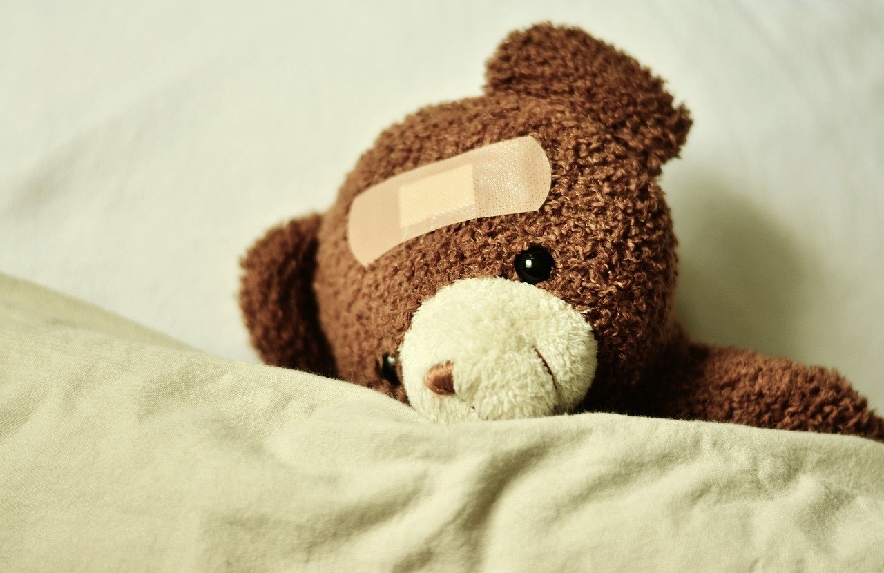 A teddy bear in bed with a headache