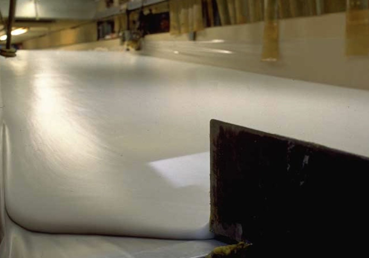 Memory foam mattress liquid being poured onto a conveyor