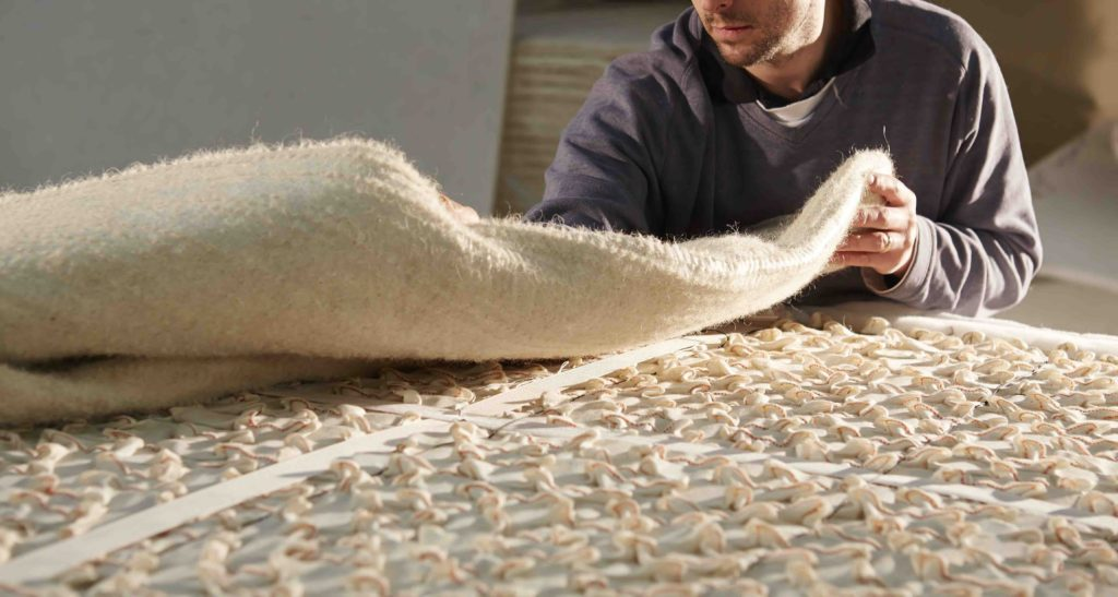 Applying the insulator layer of a natural fibre mattress