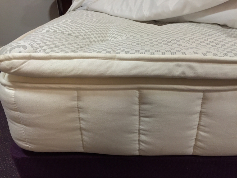 Close up of Premier Inn Hypnos pillowtop mattress on John Ryan By Design website