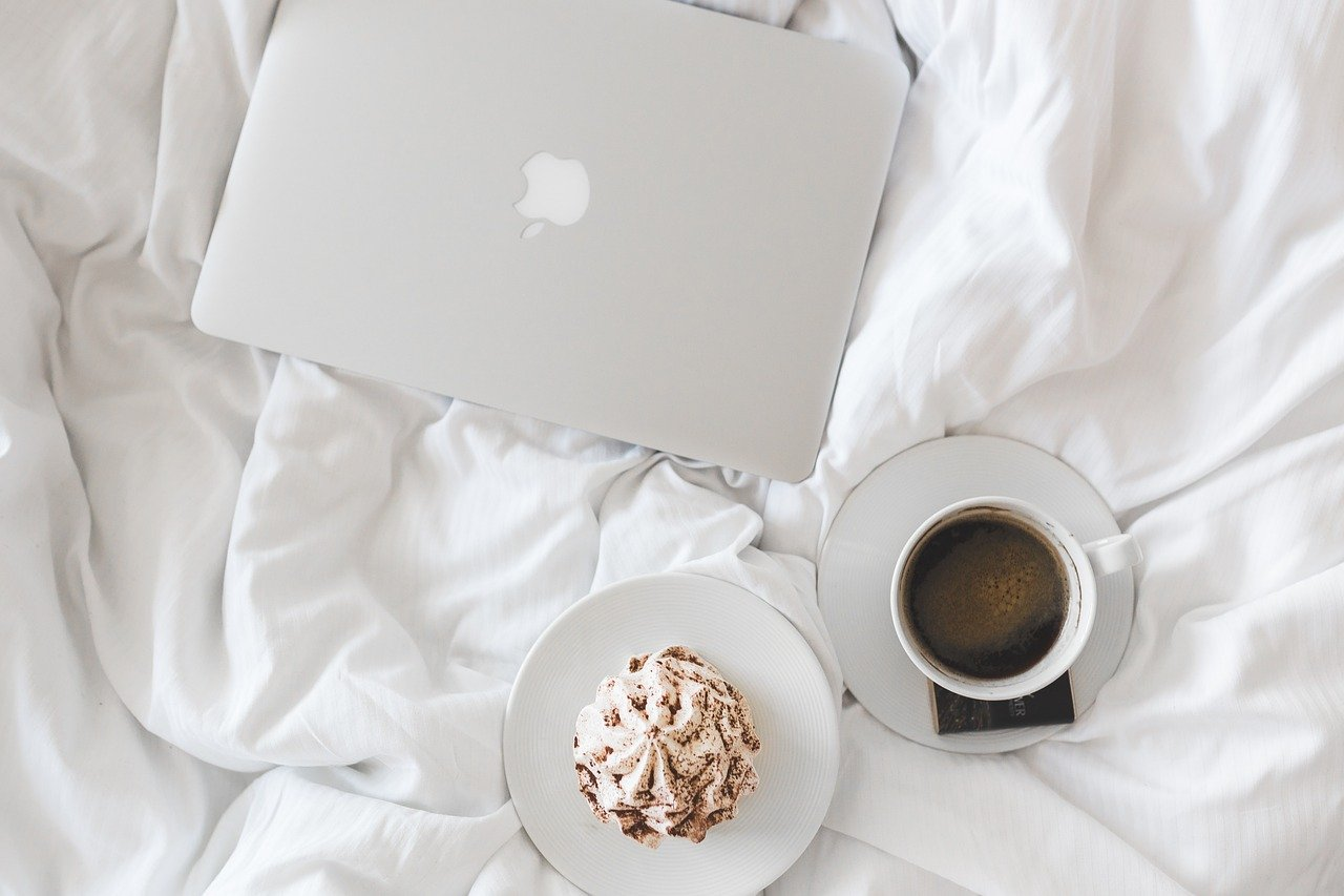 Laptop on bed with coffee and a cake