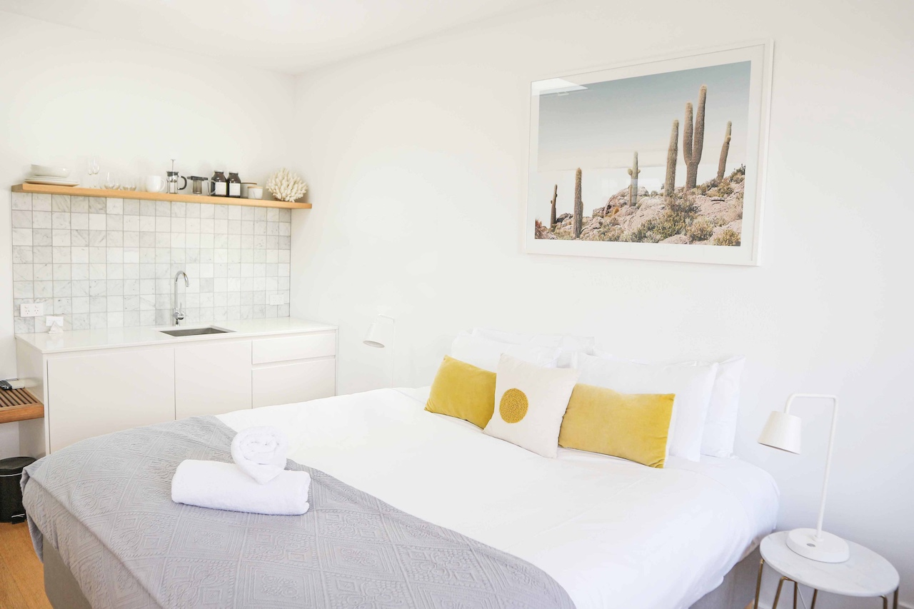A white bed in a studio apartment