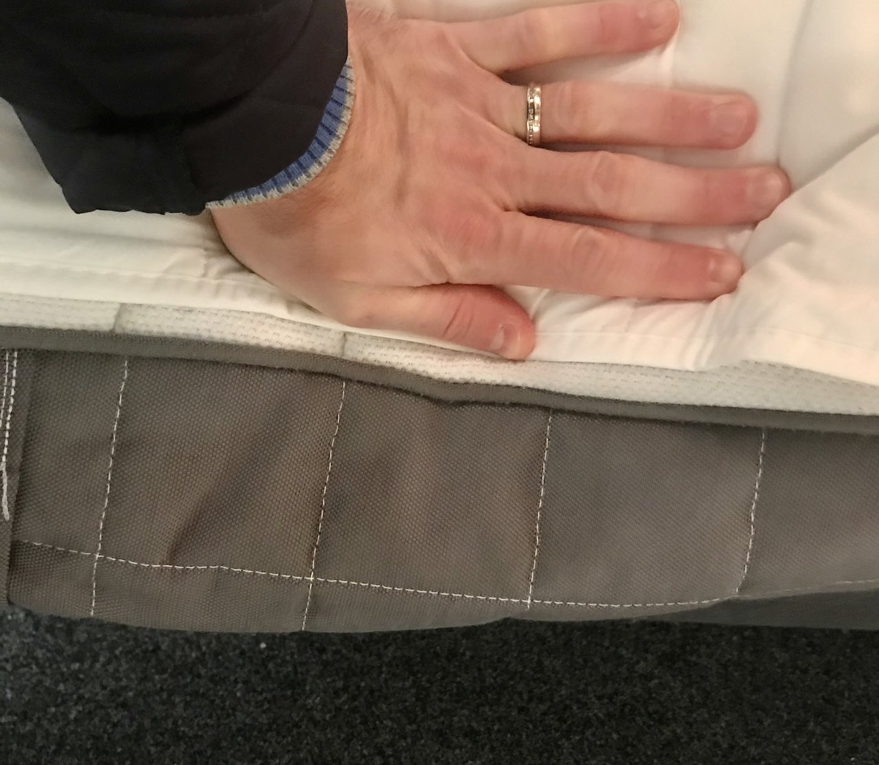A hand pushing the side of an Ikea mattress