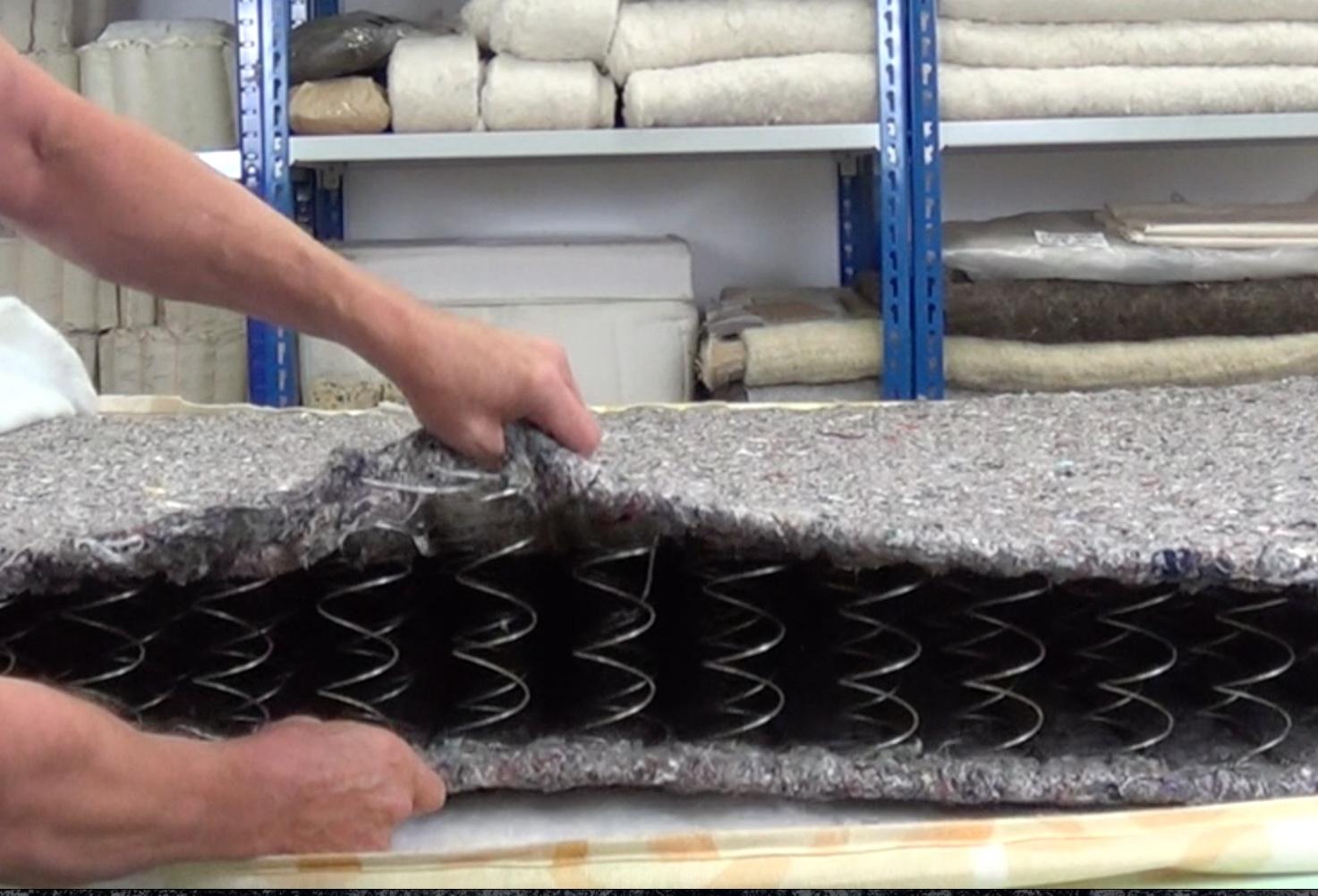 A man holding open a cage sprung mattress